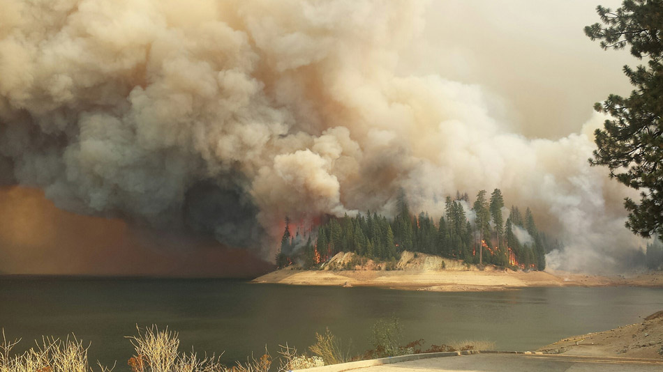 The King Fire burns trees near a body of water