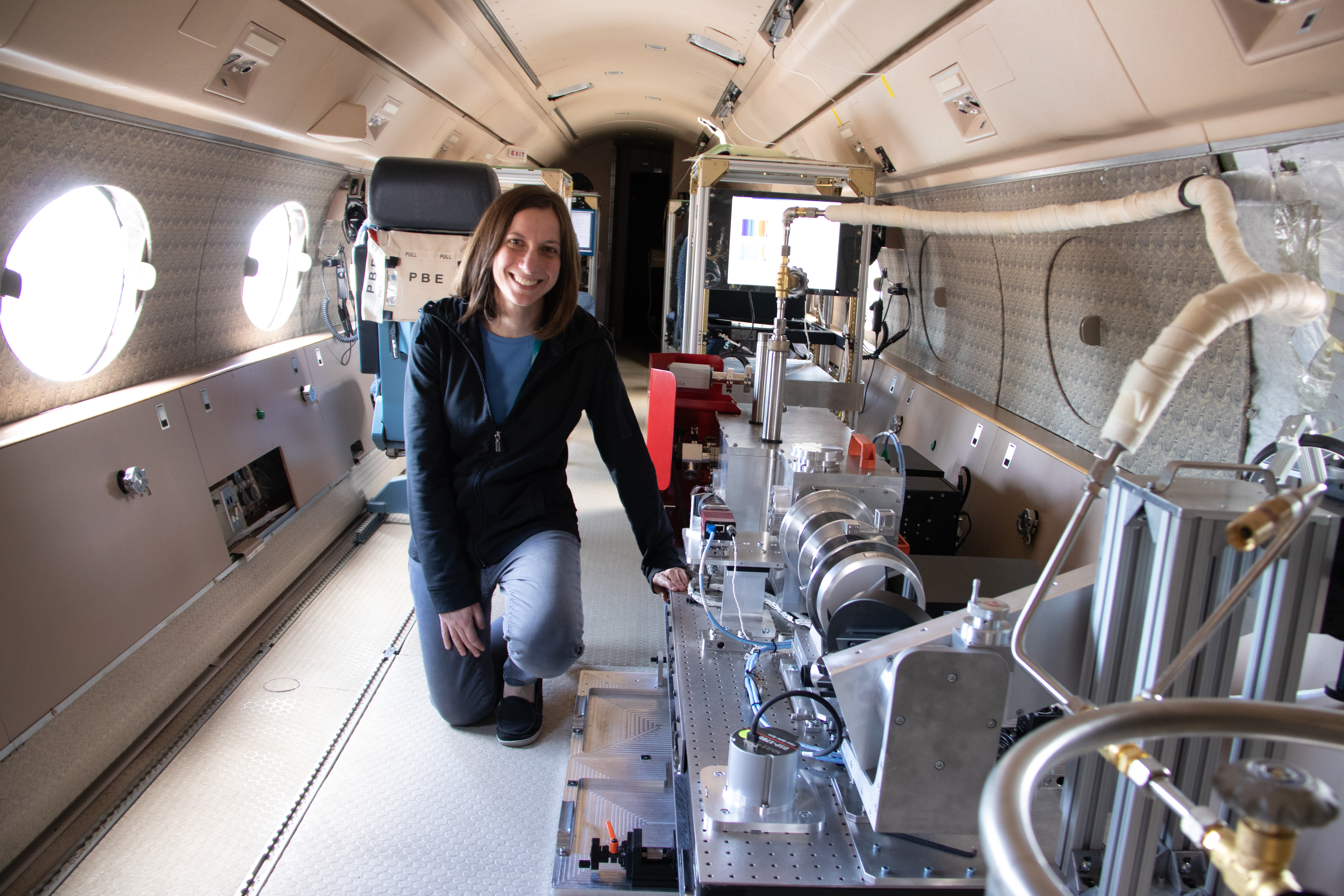Instrument scientist Jenna Samra kneels next to the Airborne InfraRed Spectrometer (AIR-Spec)