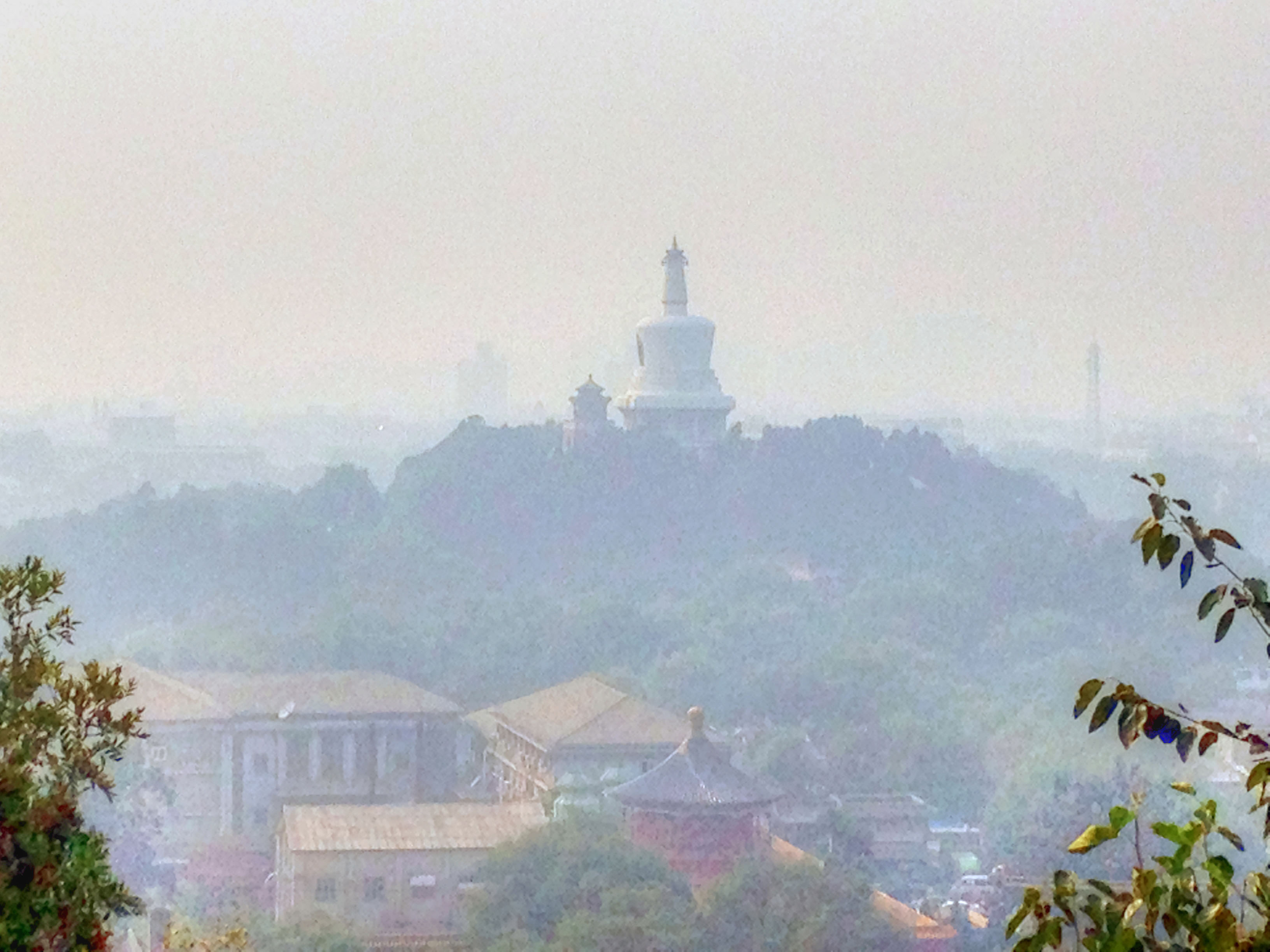 Smog obscuring the view of the white pagoda in Beijing, China.