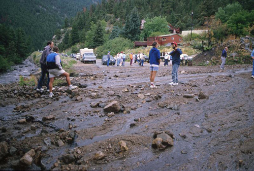 Photograph of people standing at washed-out road after flood