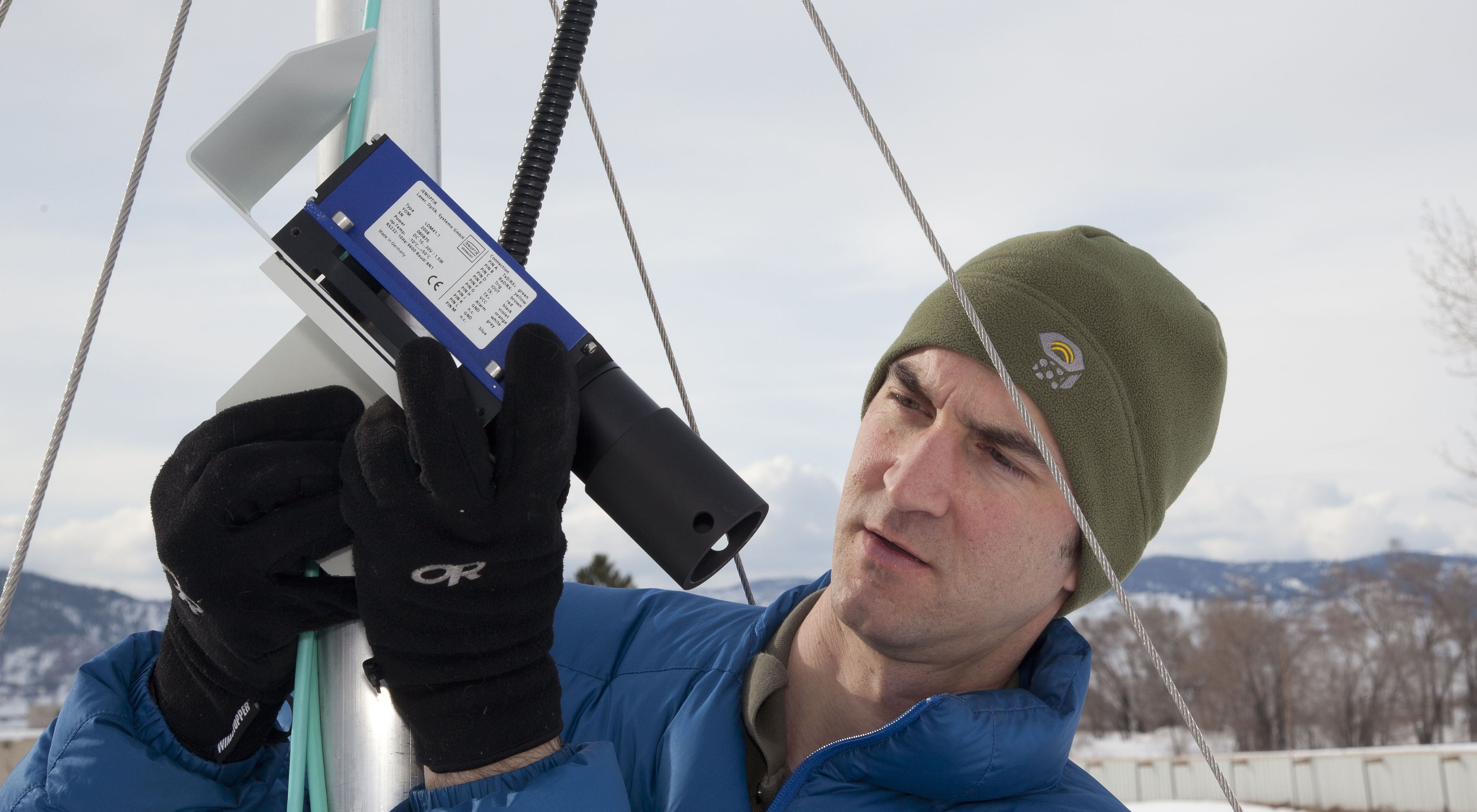 Scientist examines laser instrument for measuring snow