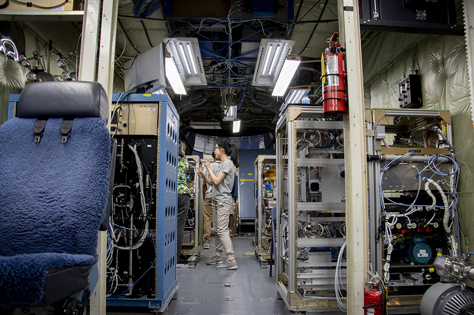 Inside the NSF/NCAR C-130 research aircraft, a scientists stands and works on her atmospheric chemistry sampling tool.