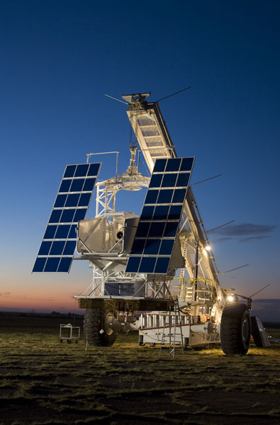 Solar panels attached to metal equipment on hill at sunrise
