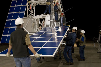 Men unloading solar panels and other equipment