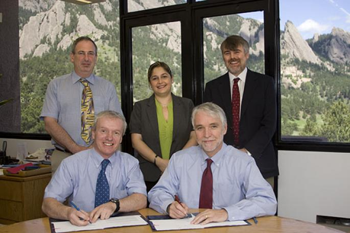 Photograph of five people, two sitting at desk, Boulder flatirons behind them