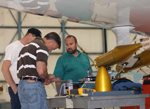 Photograph of three men in a hangar working on equipment