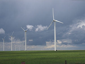 Photograph of a wind farm, cloudy sky in background
