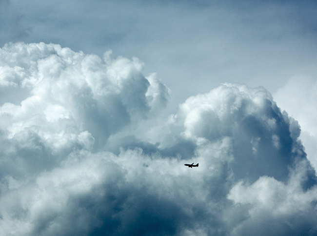 Jet flying through towering cumulus clouds