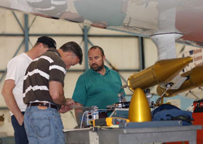 Photograph of three men in a hangar wroking on equipment  attached to a plane