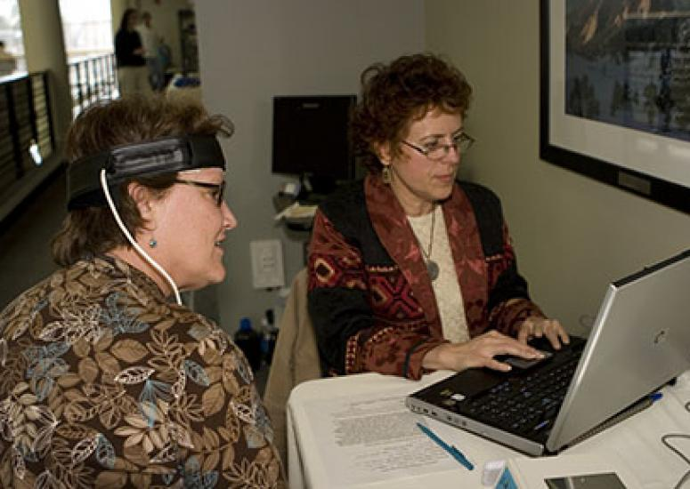 Photograph of two women sitting in an office, one undergoing a medical test