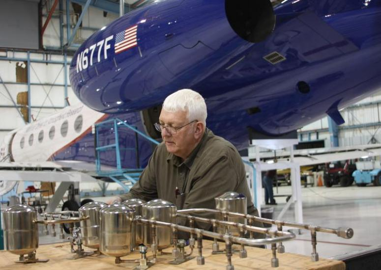Scientist works on observing instrument with aircraft behind him