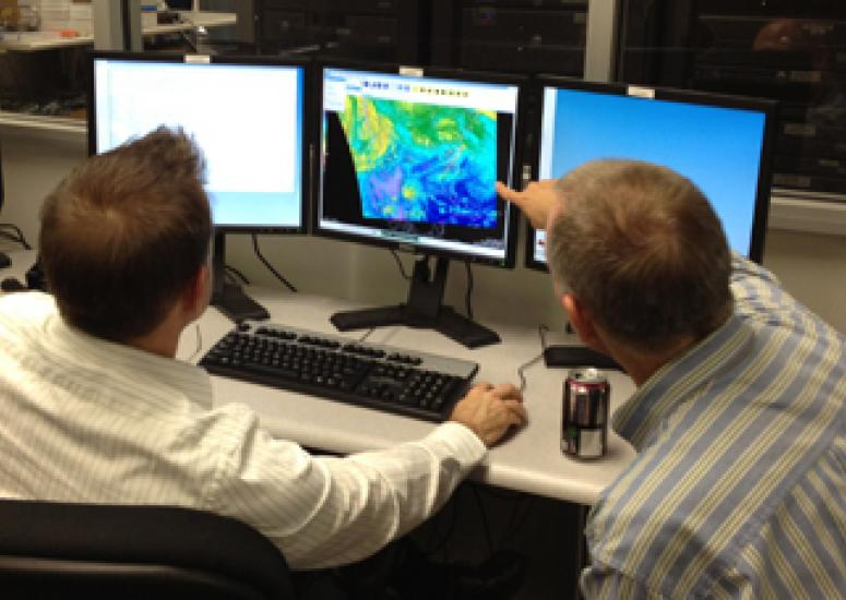 Two forecasters at the National Weather Service test-drive a graphics system.