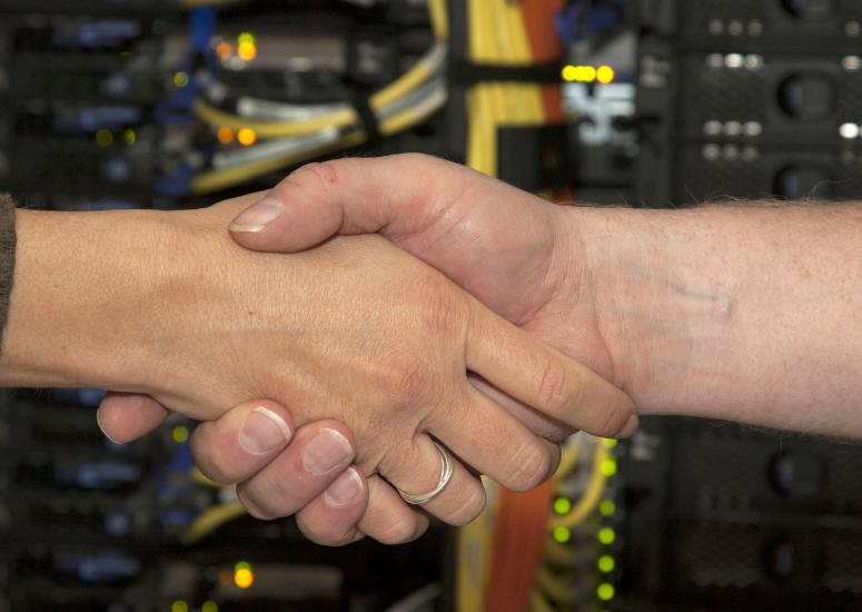 Handshake in front of supercomputer
